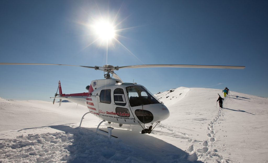 """""""Wanaka, New Zealand - August 23rd, 2012: Photo of helicopter taking off on mountain ridge whilst heliskiing with Southern Lakes Heliski, Wanaka, New Zealand."""""""