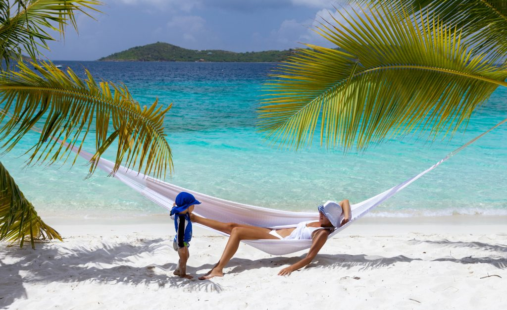 mother and child relaxing in hammock on tropical beach in the Caribbean