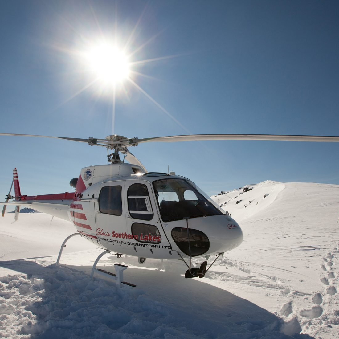 """Wanaka, New Zealand - August 23rd, 2012: Photo of helicopter taking off on mountain ridge whilst heliskiing with Southern Lakes Heliski, Wanaka, New Zealand."""