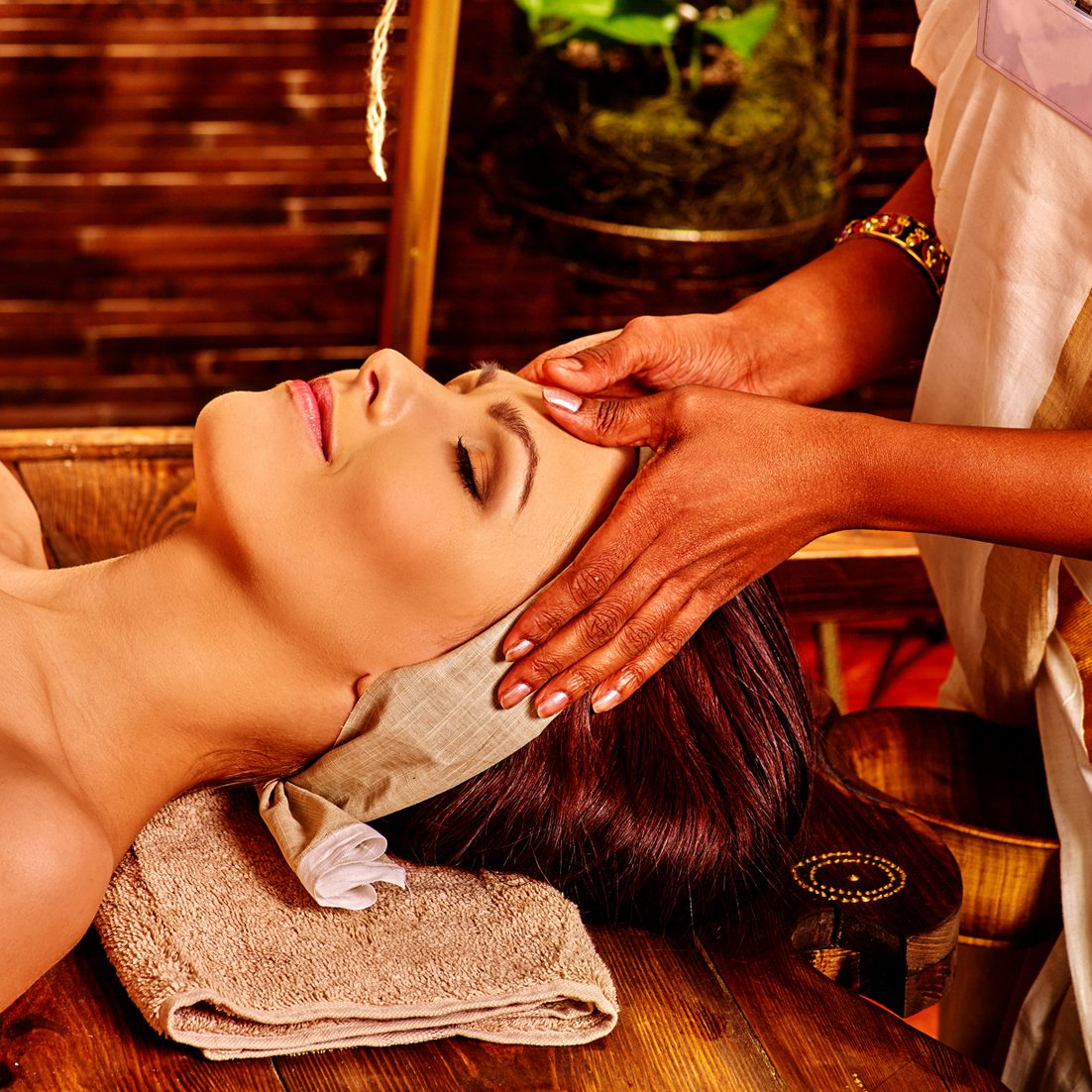 Woman having facial  ayurveda spa treatment in Indian salon.